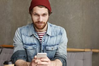 Portrait of attractive young student with thick beard wearing hat and denim jacket looking at camera with joyful smile while enjoying online communication, browsing newsfeed on social networks