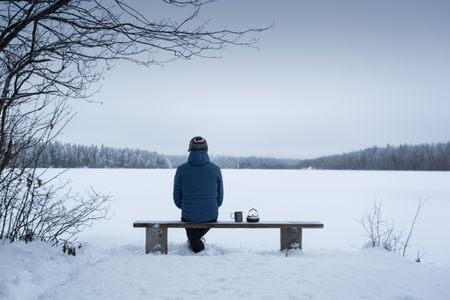 A man sits in the winter on a bench near a frozen lake. Looks at the horizon. Nearby is a kettle with a mug. The foreground is in focus, the horizon is blurred.