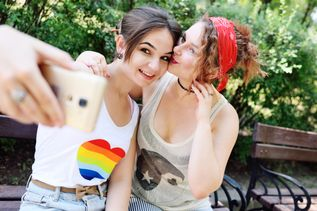 two girlfriends lesbian relieve themselves on camera phones or taking selfies and smiling