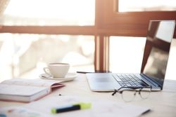 lateral-foreground-of-a-working-desk-with-the-laptop-cup-of-cof
