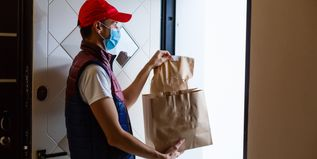Delivery man holding paper bag with food on white background, food delivery man in protective mask - 1
