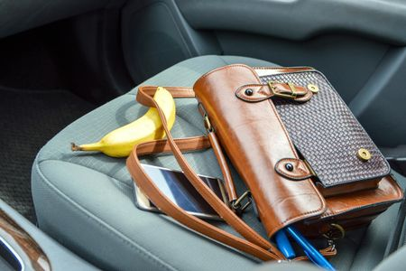 Purse and Accessories Laid Out on Passenger Seat of Car With a Banana - 1