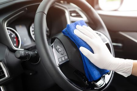 worker man wear gloves cleaning car interior console with microfiber cloth, detailing, car wash service concept. copy space.